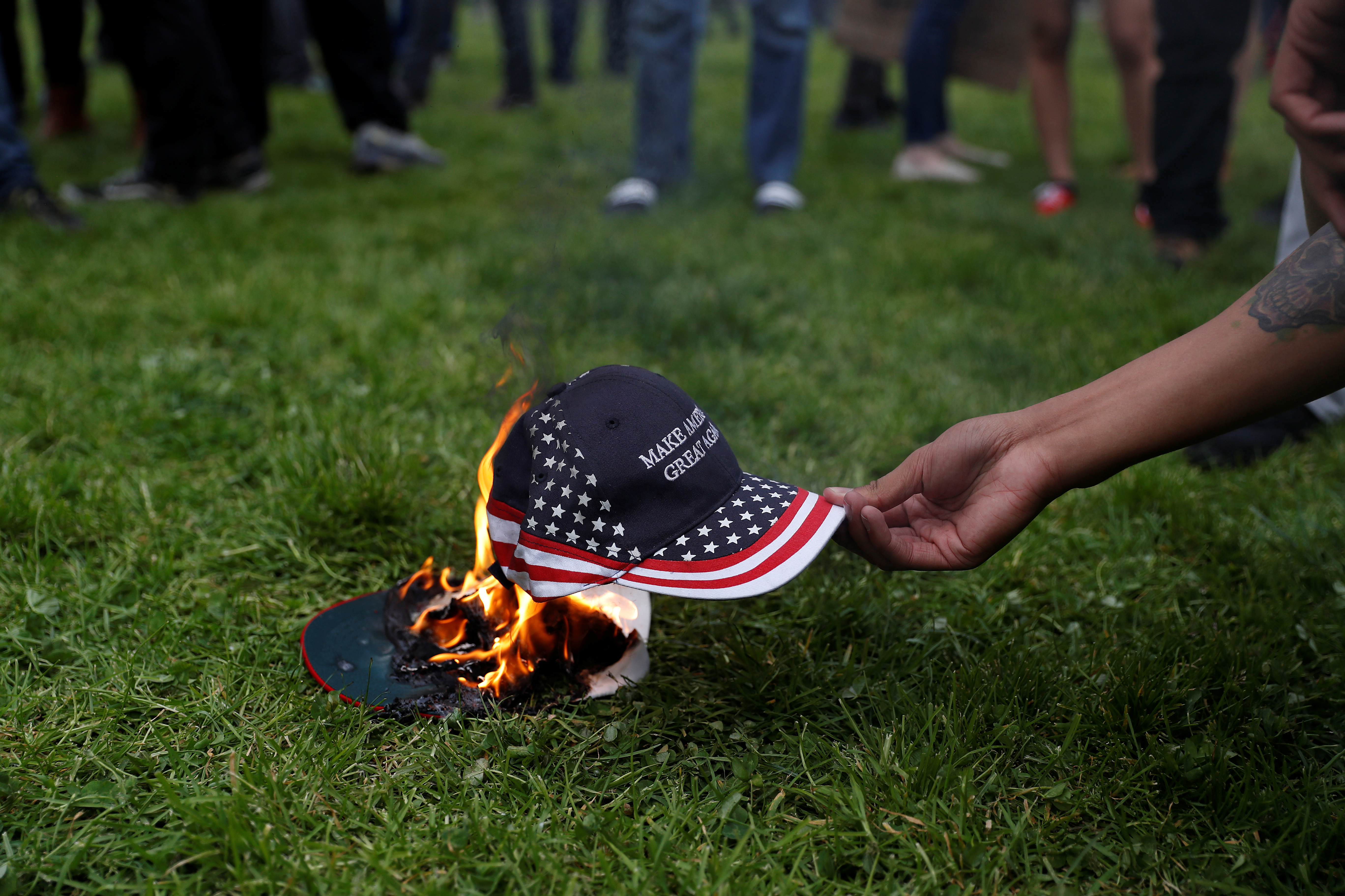 """A demonstrator in opposition of U.S. President Donald Trump sets a hat on fire during a """"People 4 Trump"""" rally in Berkeley, California"""