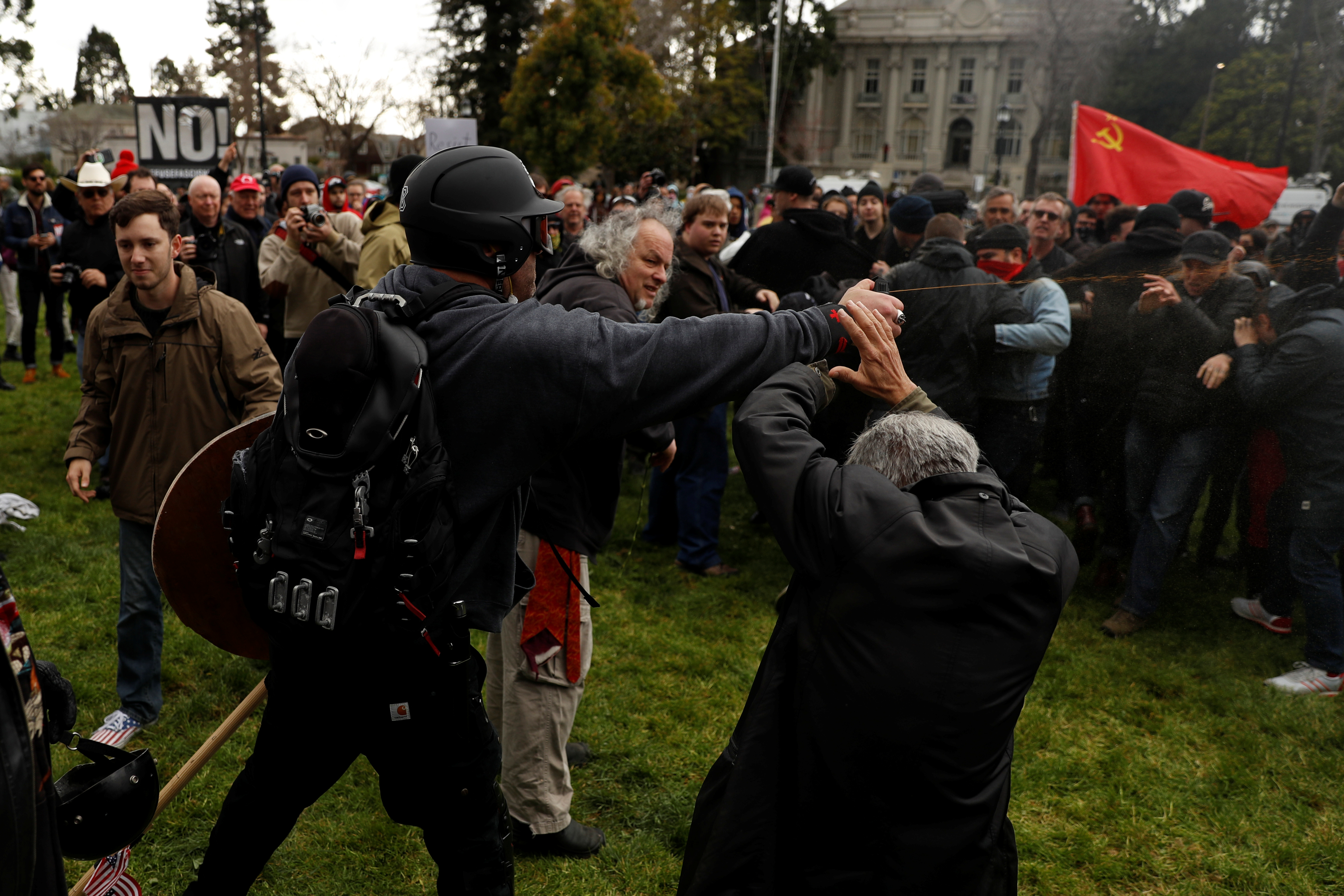 """A demonstrator in support of U.S. President Donald Trump sprays pepper spray towards a group of counter-protesters during a """"People 4 Trump"""" rally in Berkeley, California"""