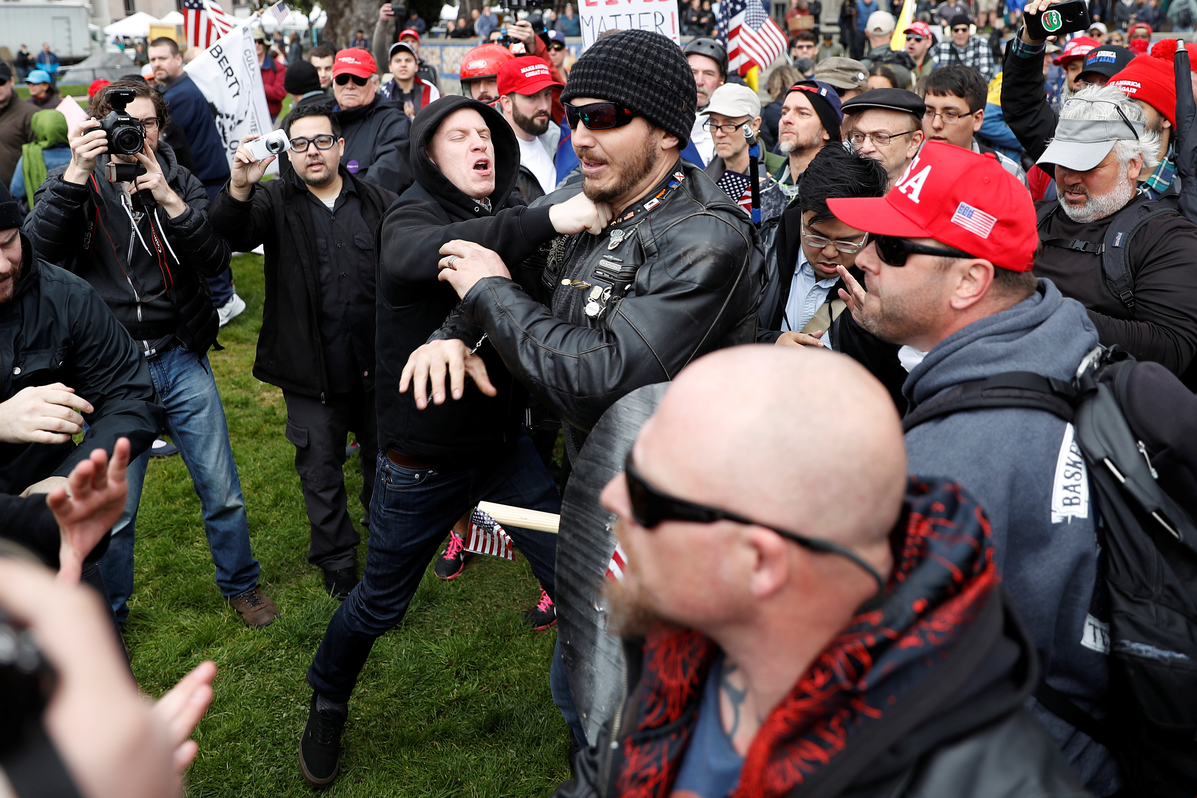 """A man (L) punches a supporter of U.S. President Donald Trump during a """"People 4 Trump"""" rally in Berkeley, California March 4, 2017. REUTERS/Stephen Lam"""