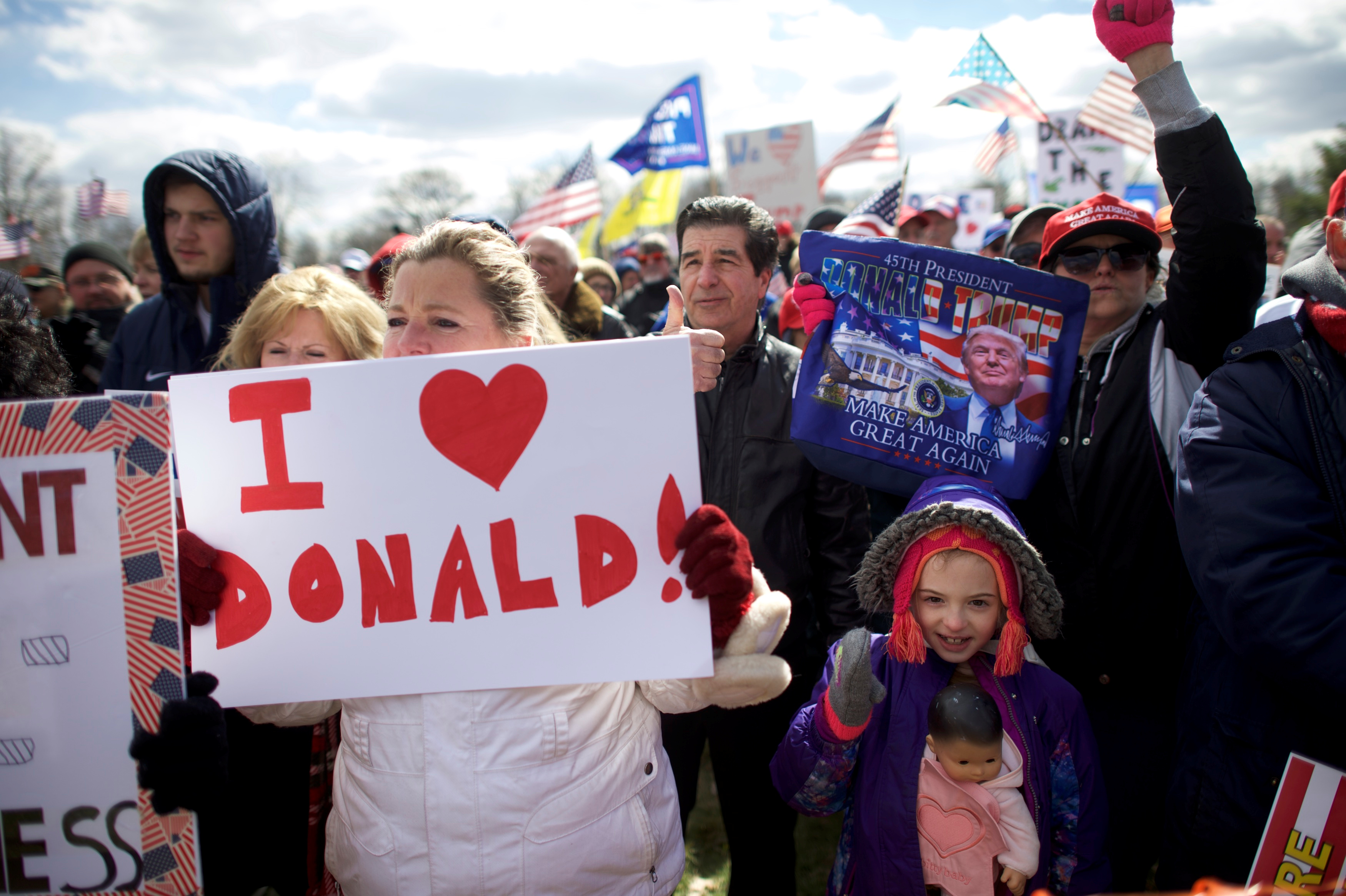 """Gia Morris, 8, carries a doll while cheering during a """"People 4 Trump"""" rally at Neshaminy State Park in Bensalem"""