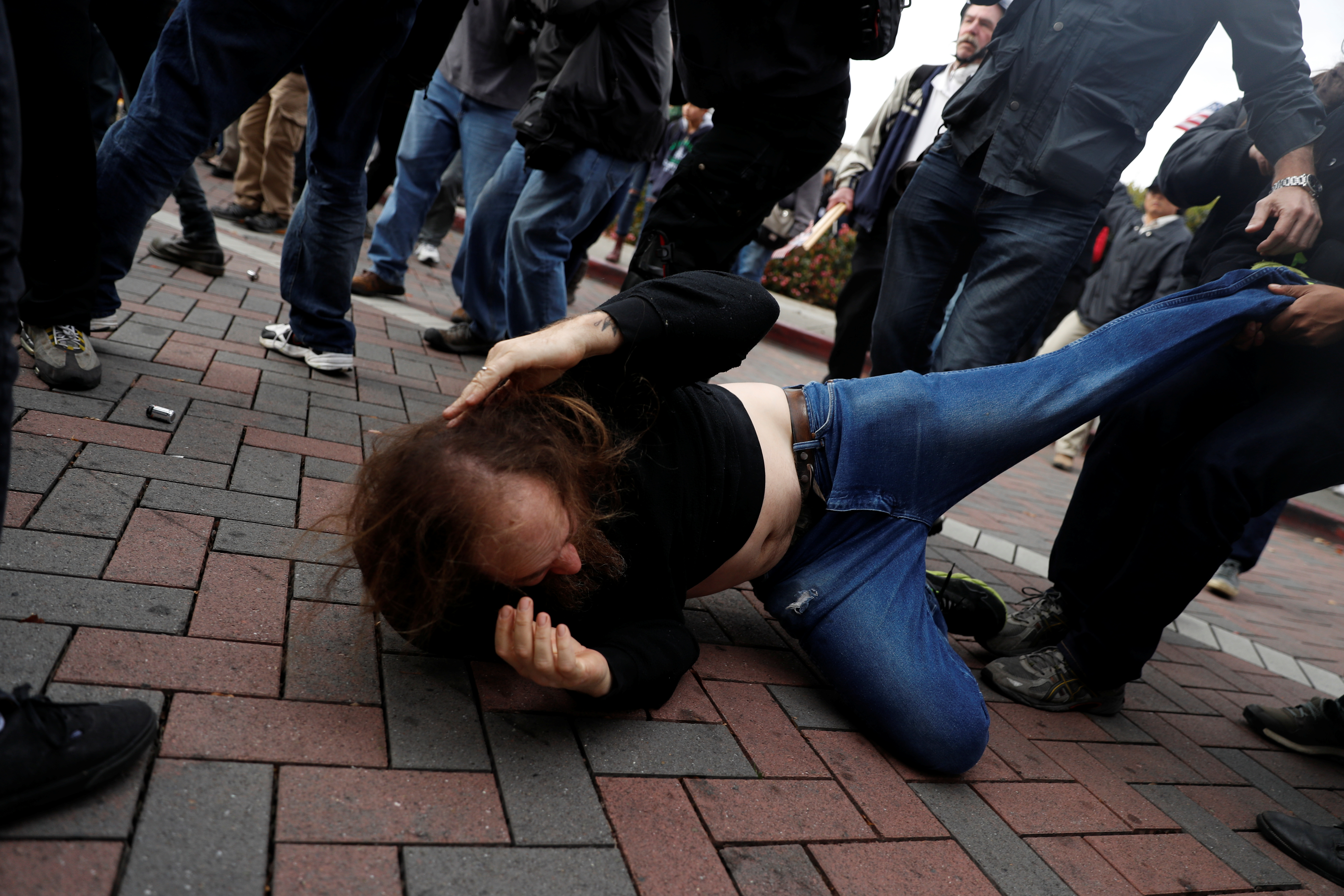 """A man is being pulled away from a scuffle as scattered fights broke out between supporters of U.S. President Donald Trump and counter-protestors during a """"People 4 Trump"""" rally in Berkeley, California"""